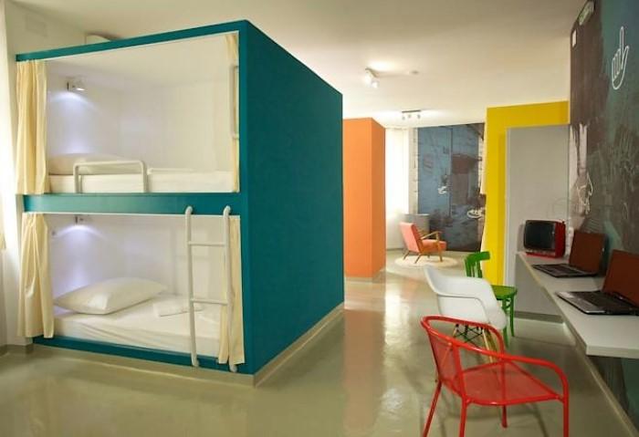 В спальне хостела оформлены столы для работы гостей, однотонный сатиновый потолок дорисовывает весь интерьер