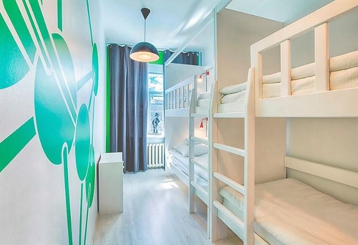 Белый сатиновый натяжной потолок в хостеле отлично дополняет интерьер общей спальни