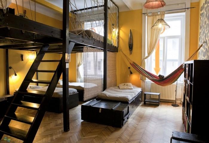 Благодаря небольшим уровневым конструкциям натяжной потолок в хостеле можно использовать для зонирования помещений